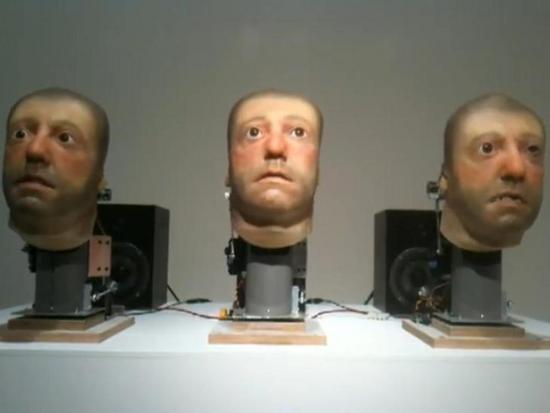 three singing robot heads